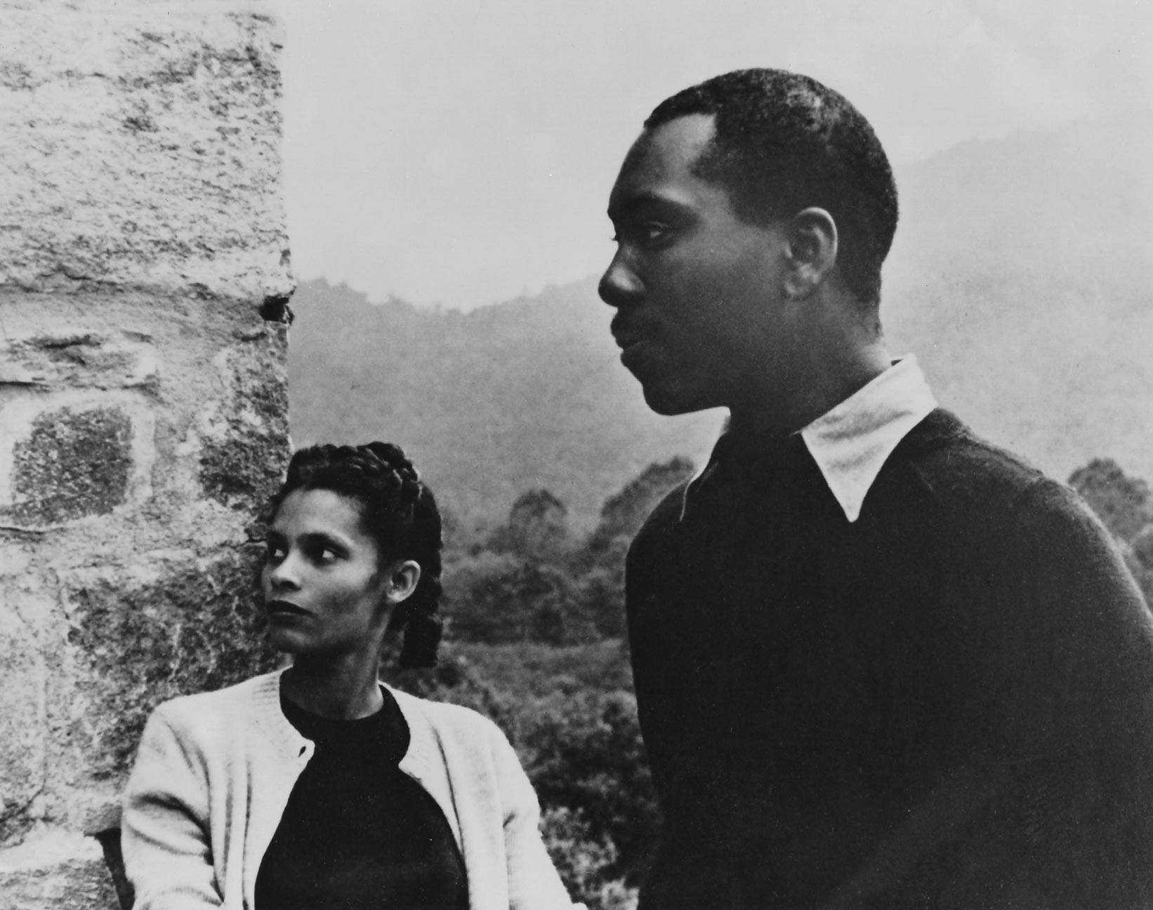 In this black and white portrait, Gwendolyn Knight and Jacob Lawrence stand by one another in profile, with the mountains behind them. Gwendolyn is leaning against a stone wall.