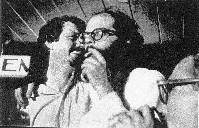 [Image] Robert Creeley and Allen Ginsberg embrace one another, Ginsberg smokes a cigarette. The two are laughing and the photo is taken from beneath by a fellow party-goer.
