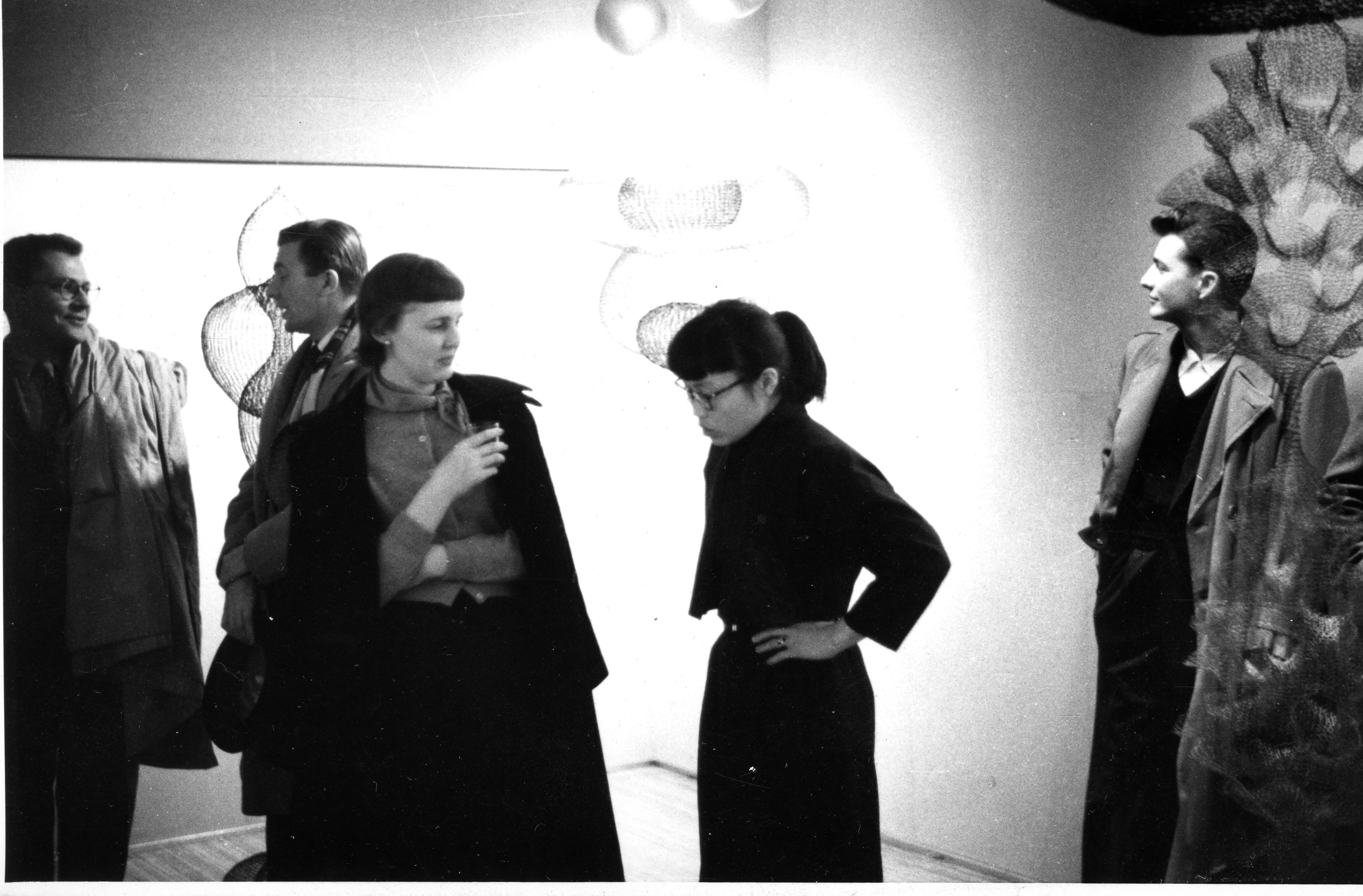 In this black and white photograph, Joan Stack (wearing a long black coat as a cape and holding a glass in her hand) speaks to Ruth Asawa who is looking down towards the ground in great focus. They are standing in front of one of Asawa's hanging wire sculptures which are 3 to 4 feet long. The light behind them is harsh and creates a halo around them both, making the sculpture hard to distinguish. A group of men stand around them talking.