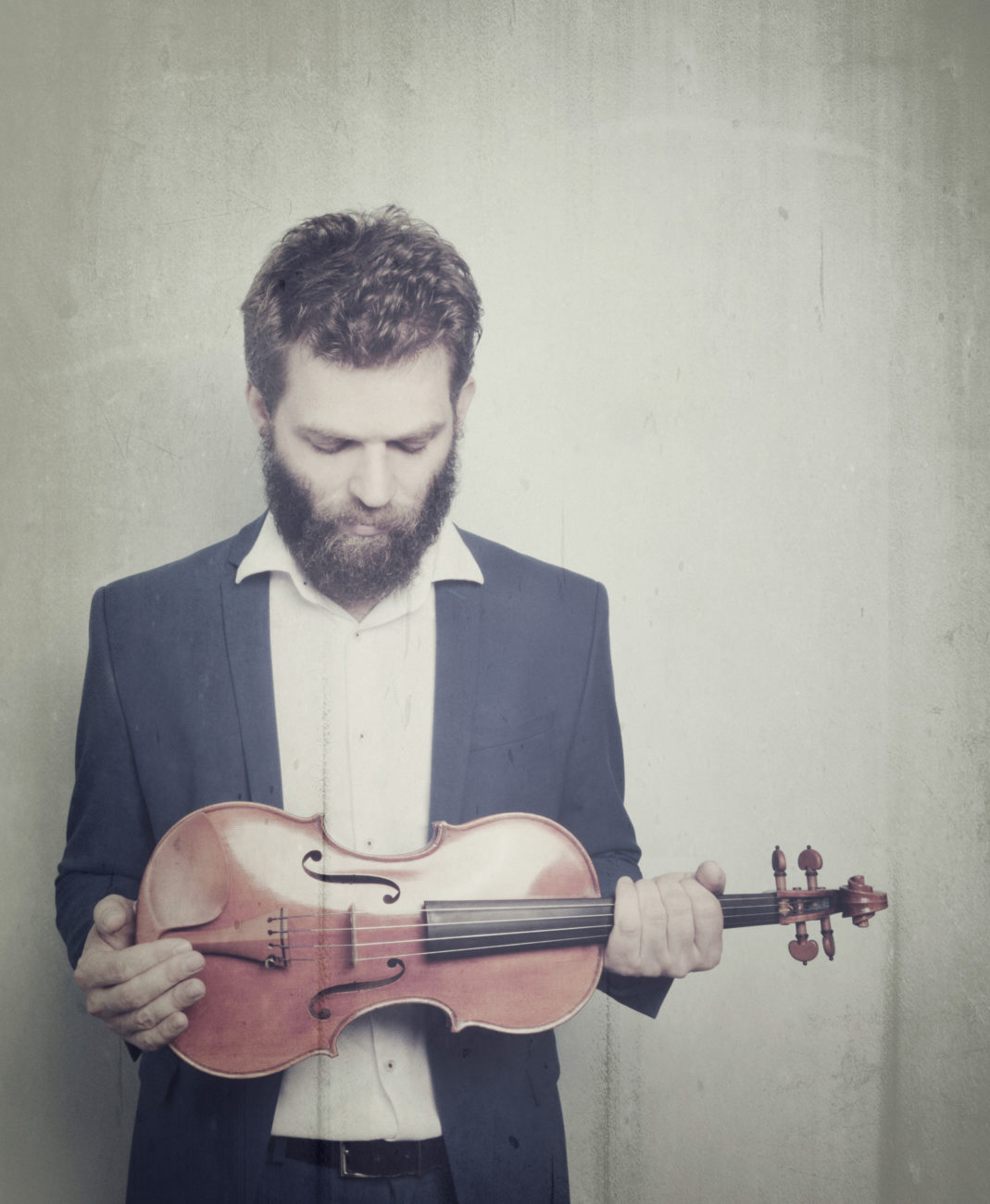 Johnny Gandelsman, a thin white man with brown hair and beard looks down at a violin which he holds in both hands at his waist.
