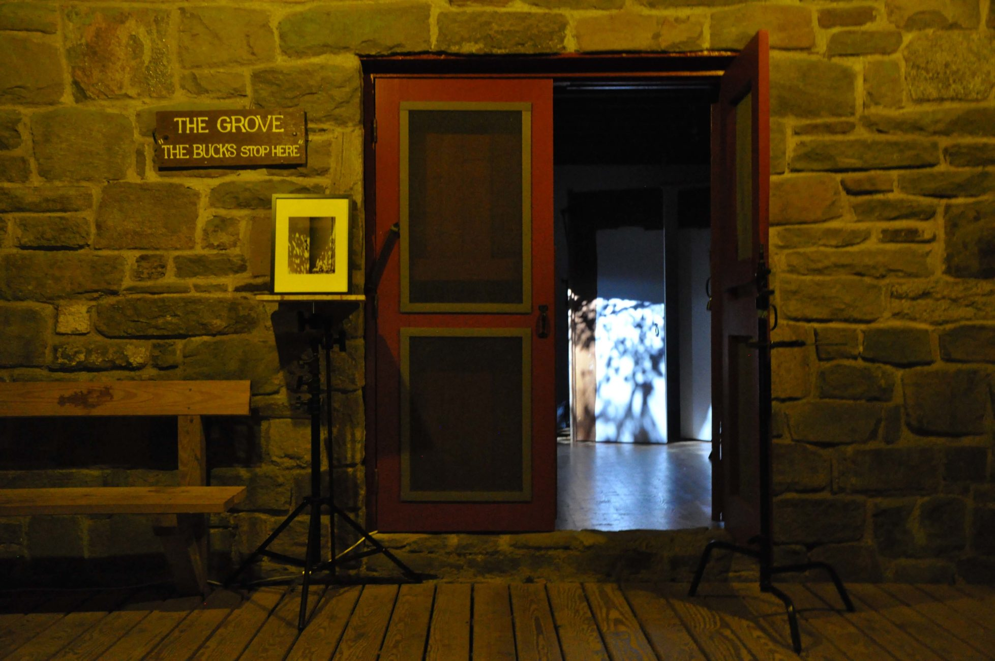 The exterior of a stone building with the red doors ajar. To the left of the doors is a small photograph of the same building but from the 1940s, photographed with light shining through leaves onto the white doors that were one there. Inside the building, seen through the open door, is a replica of that photograph with white painted wooden doors and projected images of dappled light.
